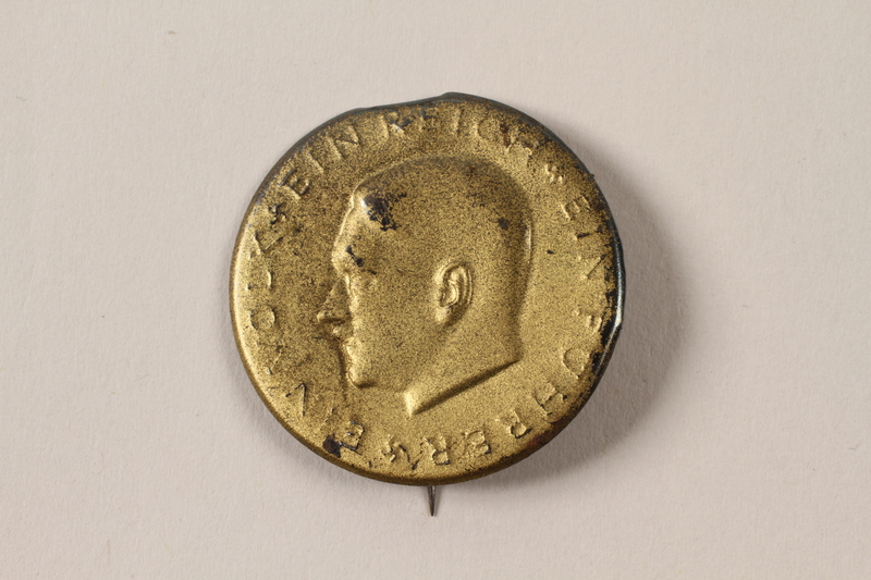 2007.477.1 front Pin with a profile of Adolf Hitler found during postwar reconstruction
