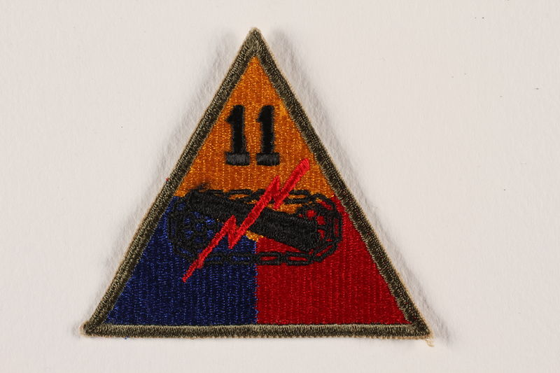 2004.749.1 front US Army 11th Armored Division shoulder sleeve patch with tank tracks, gun, and red lightning bolt