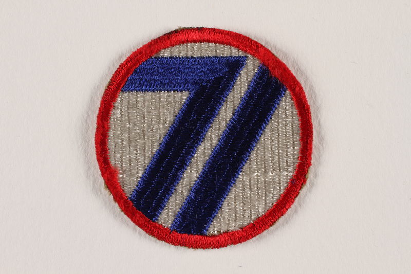 2004.749.14 front US Army 71st Infantry Division shoulder sleeve patch with a blue 71 on a red rimmed white circle