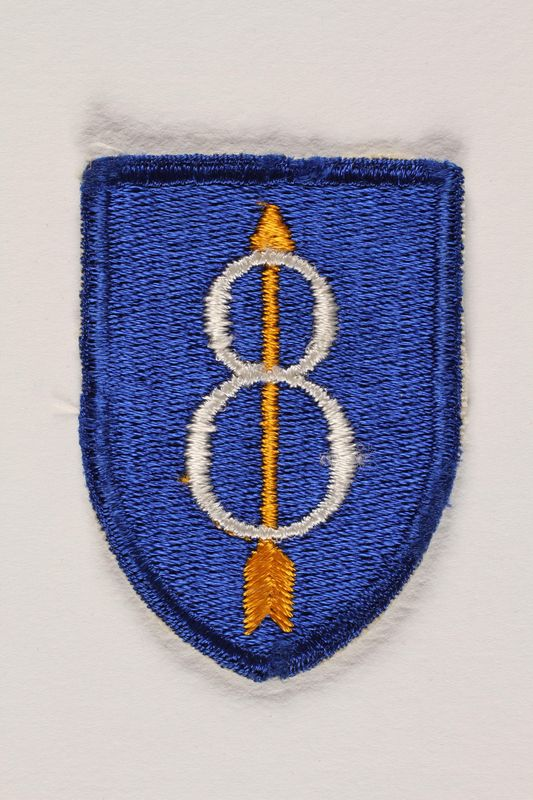 2004.749.15 front US Army 8th Infantry Division shoulder sleeve patch with an 8 pierced by a yellow arrow