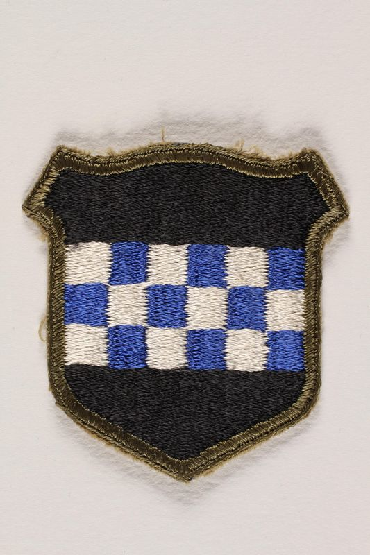 2004.749.19 front US Army 99th Infantry Division shoulder sleeve patch with a blue and white checkerboard