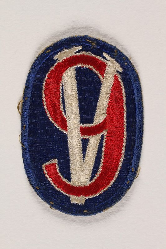 2004.749.22 front US Army 95th Infantry Division shoulder sleeve patch with a 9 on a Roman numeral V