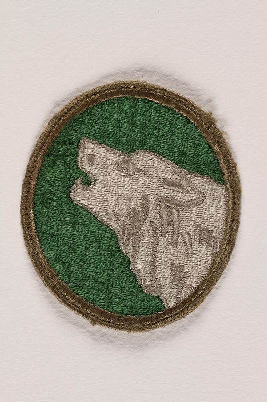 2004.749.23 front US Army 104th Infantry Division shoulder sleeve patch with a howling gray timberwolf
