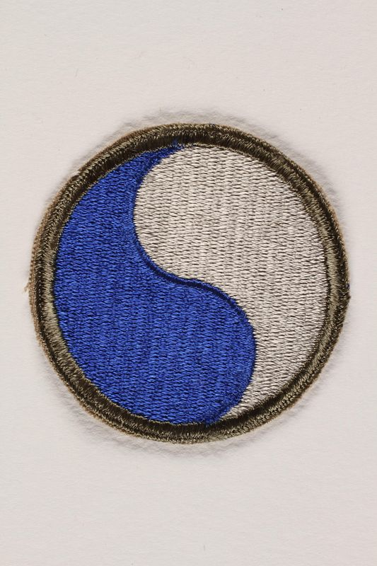 2004.749.24 US Army 29th Infantry Division shoulder sleeve patch with a blue and gray monad