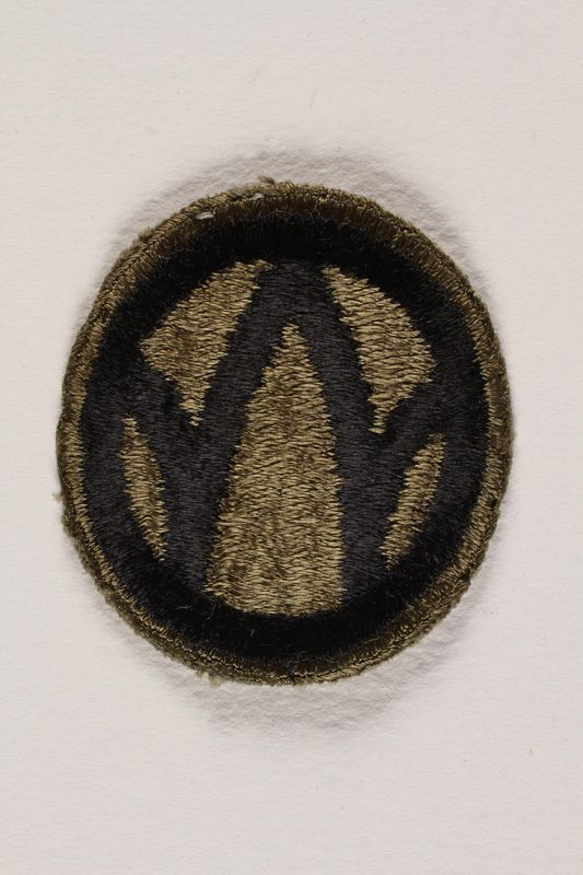 2004.749.26 front US Army 89th Infantry Division shoulder sleeve patch with a black W monogram on a green field