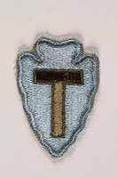 2004.749.27 front US Army 36th Infantry Division shoulder sleeve patch with a T monogram on a light blue field  Click to enlarge