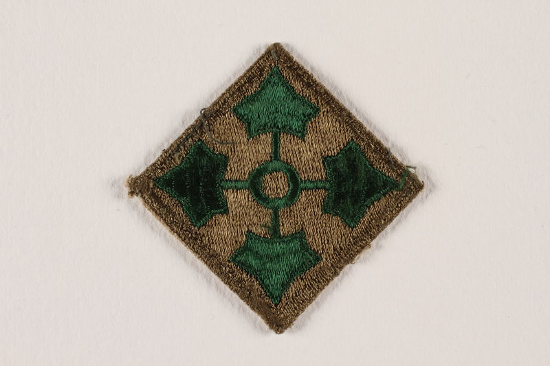 2004.749.29 front US Army 4th Infantry Division shoulder sleeve patch with 4 green ivy leaves on a brown field