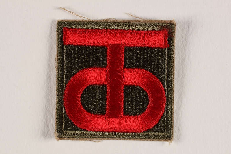 2004.749.30 front US Army 90th Infantry Division shoulder sleeve patch with a red T and O monogram on a black field