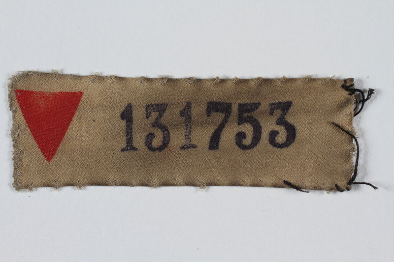 1999.100.39 front Prisoner patch with red triangle and number owned by a German Jewish displaced person and camp survivor