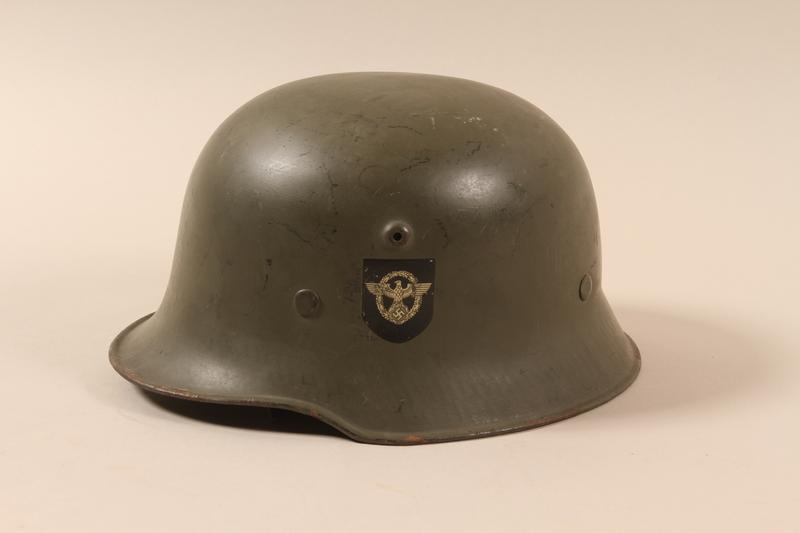 1990.297.2 left side Schutzpolizei [Security police] helmet taken from a captured German by a US soldier