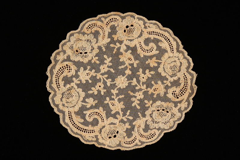 2008.220.3 front White net doily with embroidered flowers recovered by a Dutch Jewish family
