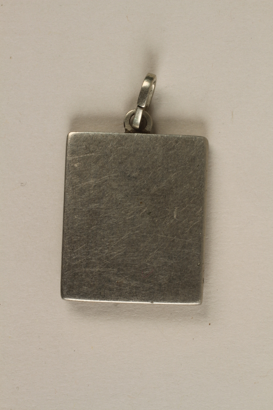 2006.363.4 back Miniature metal picture frame pendant made in Theresienstadt concentration camp