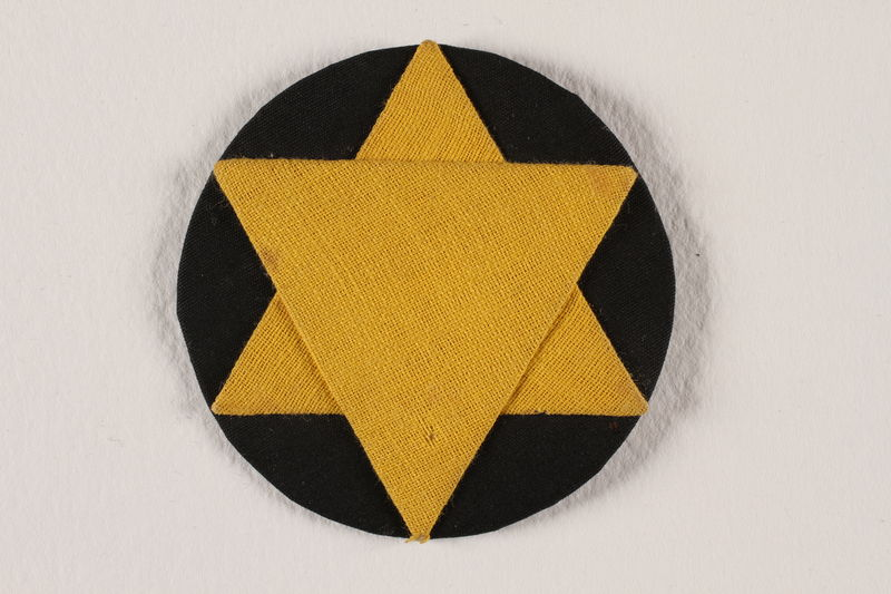 2009.105.1 front Star of David badge with a yellow star on a black circle worn by a Jewish Romanian woman