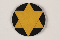 2009.105.1 front Star of David badge with a yellow star on a black circle worn by a Jewish Romanian woman  Click to enlarge