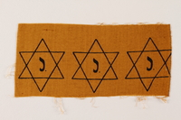 2007.14.3 front Sheet of three uncut, factory-printed Star of David badges printed with a J acquired by a Belgian Catholic rescuer  Click to enlarge
