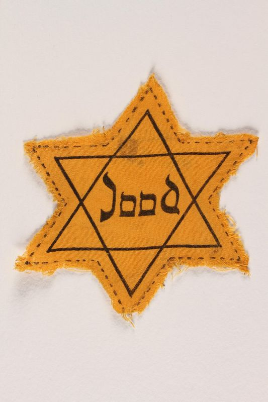 1990.307.12 front Factory-printed Star of David badge printed with Jood, belonging to a German Jewish refugee