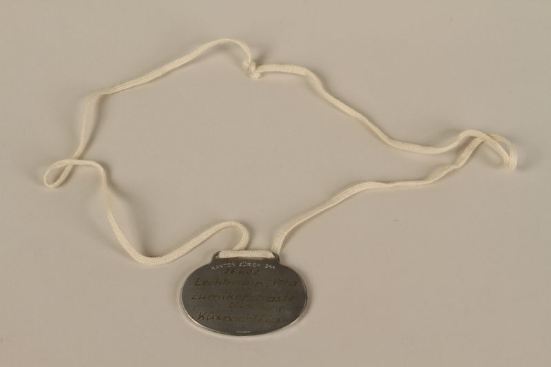 2008.319.1 back Identification tag with name and birthdate issued to a Jewish refugee child