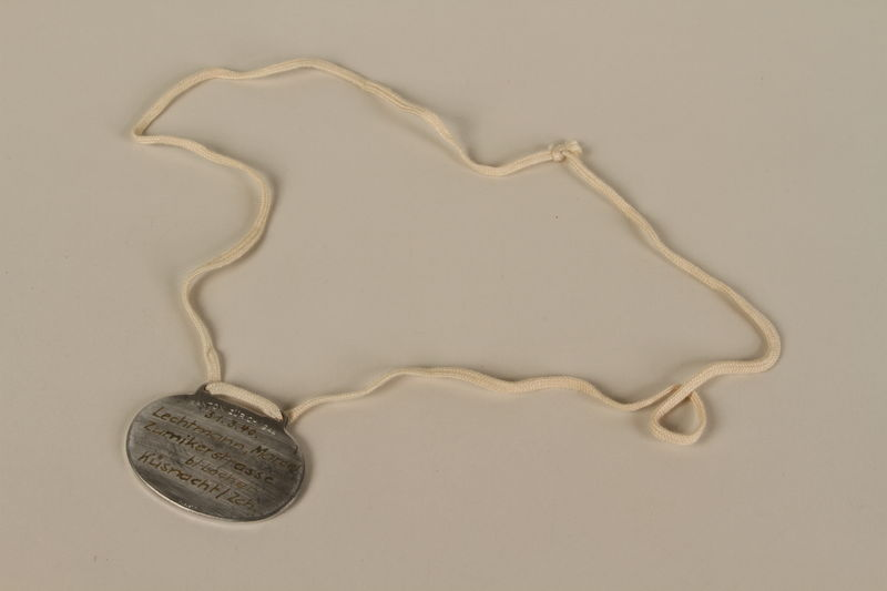 2008.319.2 back Identification tag with name and birthdate issued to a Jewish refugee child