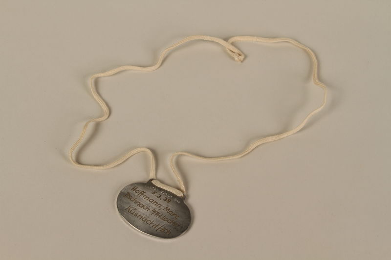 2008.319.4 back Identification tag with name and birthdate issued to a Jewish refugee child
