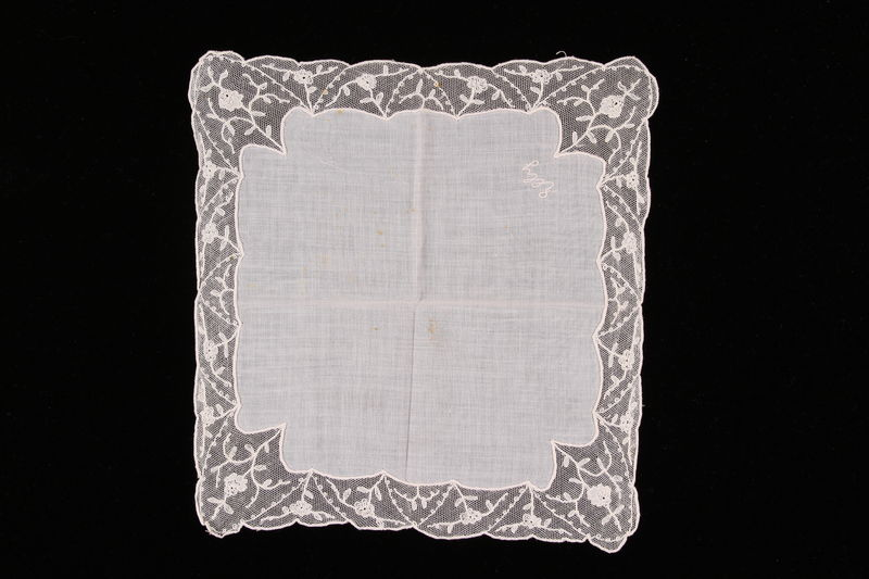 2009.117.6 front Embroidered white handkerchief with floral lace border brought with a Polish Jewish emigre