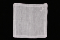 2009.117.11 front Embroidered white handkerchief with woven lines brought with a Polish Jewish emigre  Click to enlarge