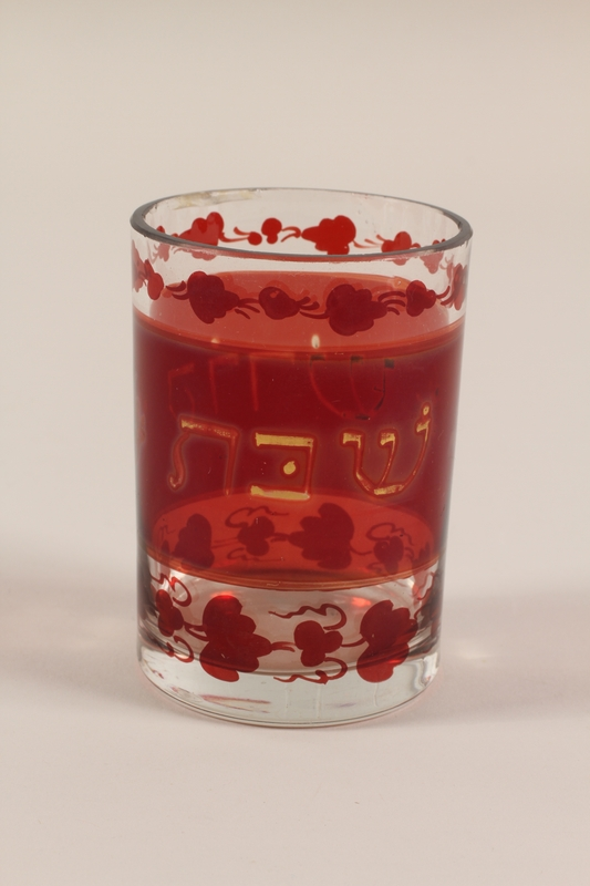 2009.118.2 front Glass kiddush cup with red and gold bands and the Hebrew word Shabbat saved from the Warsaw ghetto