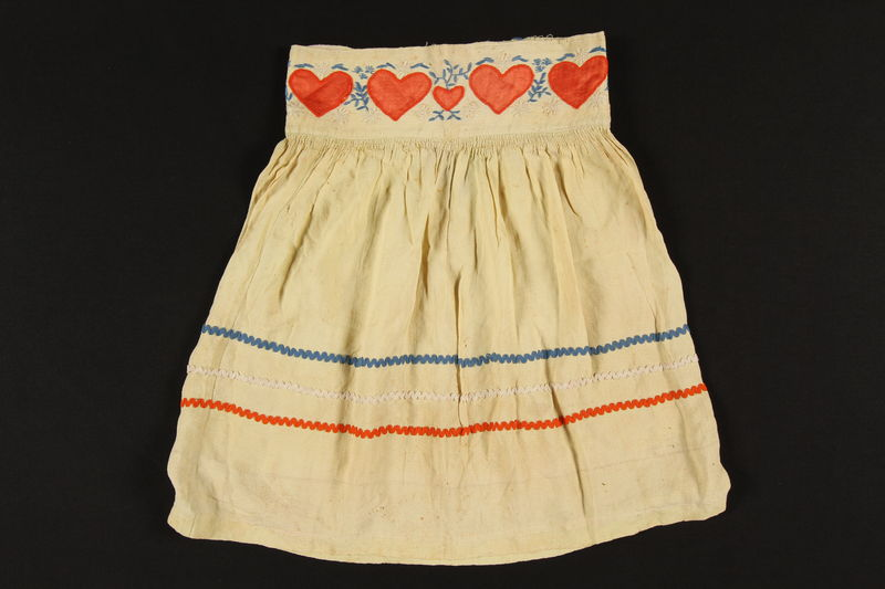 2009.120.2 front Child's yellow skirt with heart patches made for an abandoned hidden child by her rescuer