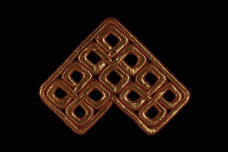 2009.117.22 front Metallic bronze tallit decoration of entwined squares brought with a Polish Jewish emigre