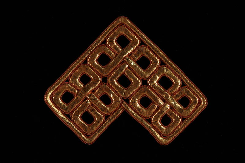 2009.117.23 front Metallic bronze tallit decoration of entwined squares brought with a Polish Jewish emigre