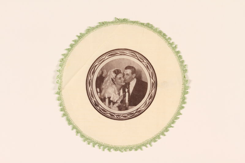 2009.150.3 front Doily printed with the wedding photograph of a young couple married in a displaced persons camp