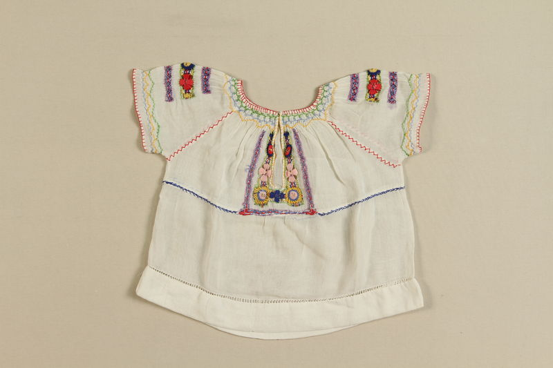 2008.349.3 front Child's white blouse with red, yellow, and pink floral embroidery worn by 2 sisters  prior to living in hiding