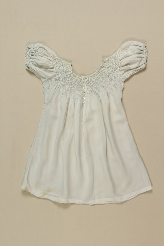 2008.349.4 front Child's white smocked dress worn by 2 sisters while living in hiding