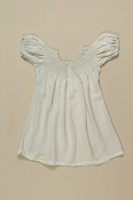 2008.349.4 front Child's white smocked dress worn by 2 sisters while living in hiding  Click to enlarge