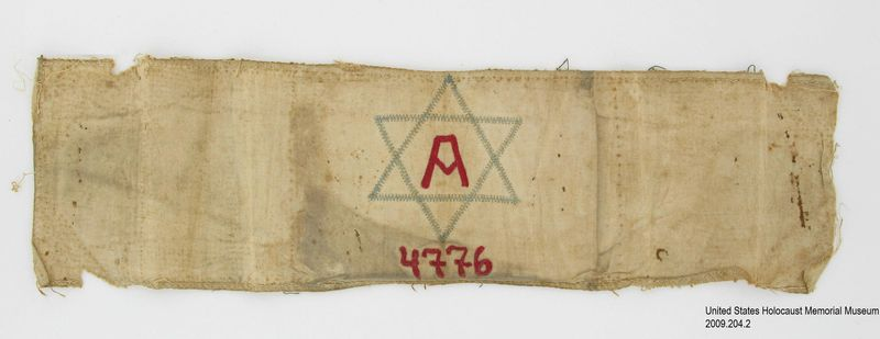 """2009.204.2 front Arbeiter [Laborer] armband embroidered with a Star of David and a red letter """"A"""" worn in the Lvov ghetto"""
