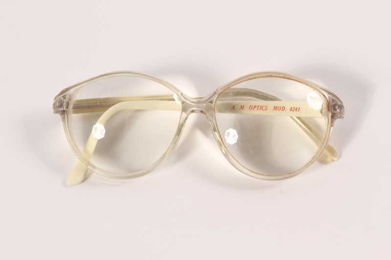 2009.204.6 front Clear and white plastic eyeglasses worn by a Jewish emigrant