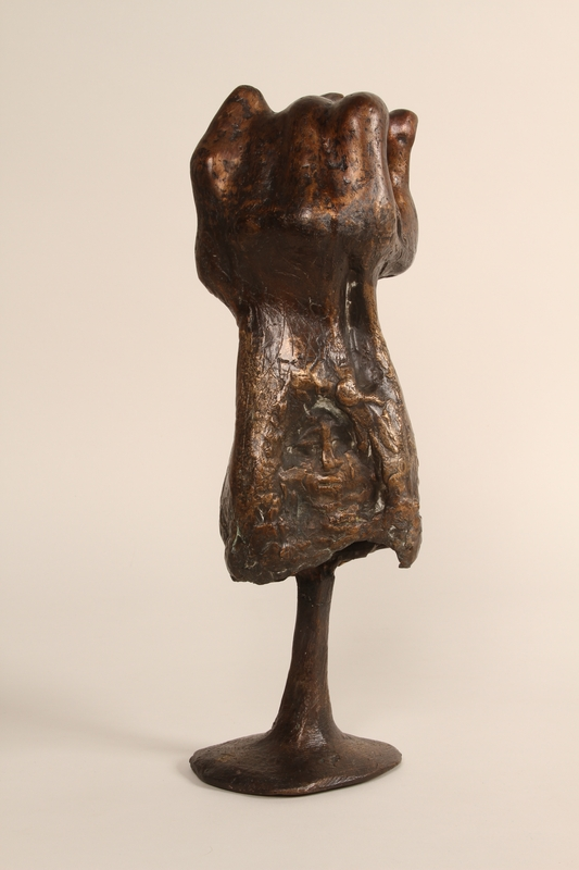 1990.337.1 back. Bronze sculpture of a woman resting in the shelter of a cupped hand
