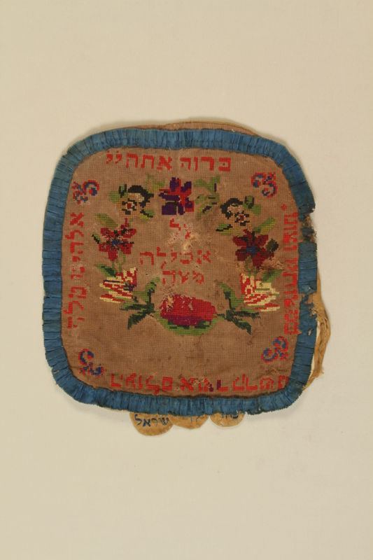 1990.41.2_a front Needlepoint matzoh cover with a Hebrew inscription, flowers and leaves