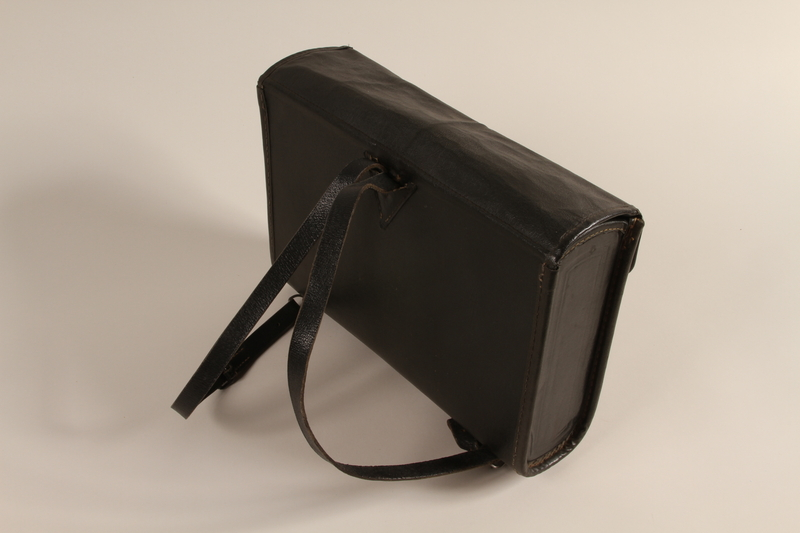 1990.44.1 back Black leather covered fiberboard knapsack used by a student in Nazi Germany