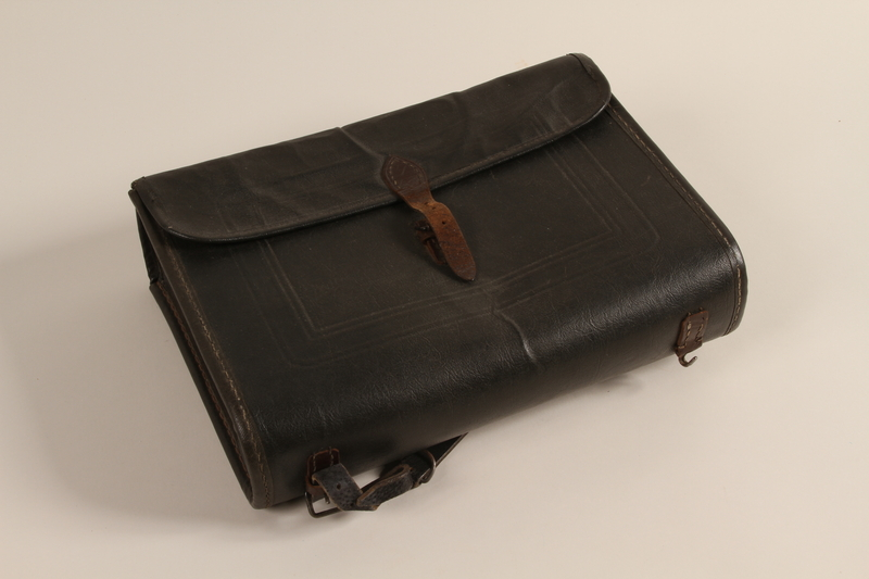 1990.44.1 front Black leather covered fiberboard knapsack used by a student in Nazi Germany