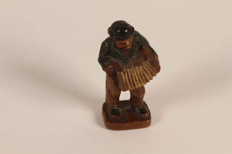 2008.362.2 front Figurine of a man in folk costume playing an accordion brought to the US by a Jewish refugee from prewar Germany