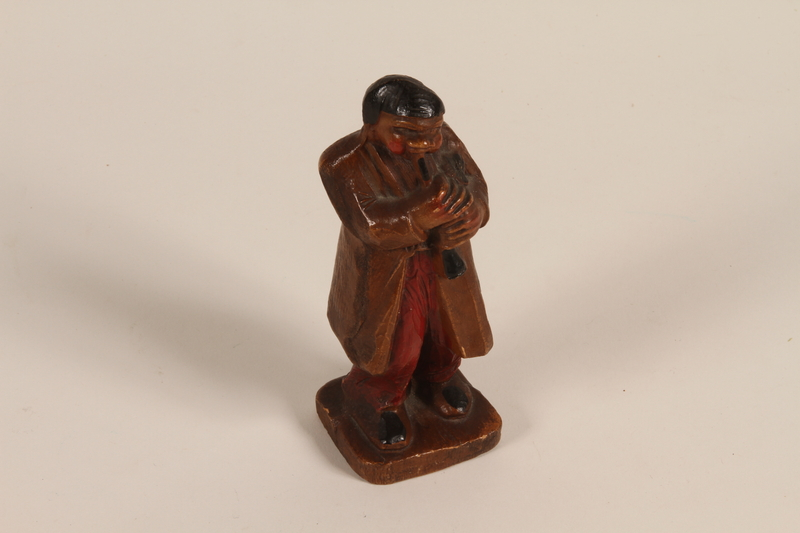 2008.362.3 front Figurine of a man in folk costume playing a clarinet brought to the US by a Jewish refugee from prewar Germany