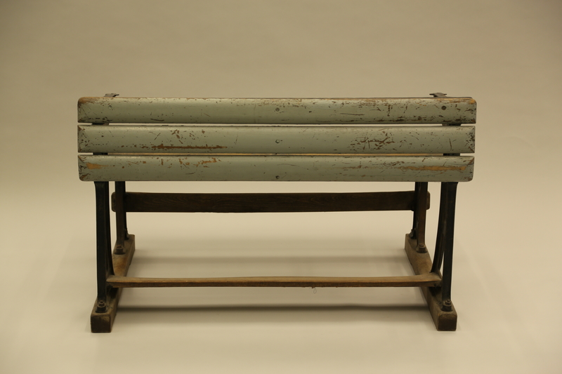 1990.44.7 front Slatted wooden desk with attached bench on wrought iron supports used in a Dresden schoolroom in Nazi Germany
