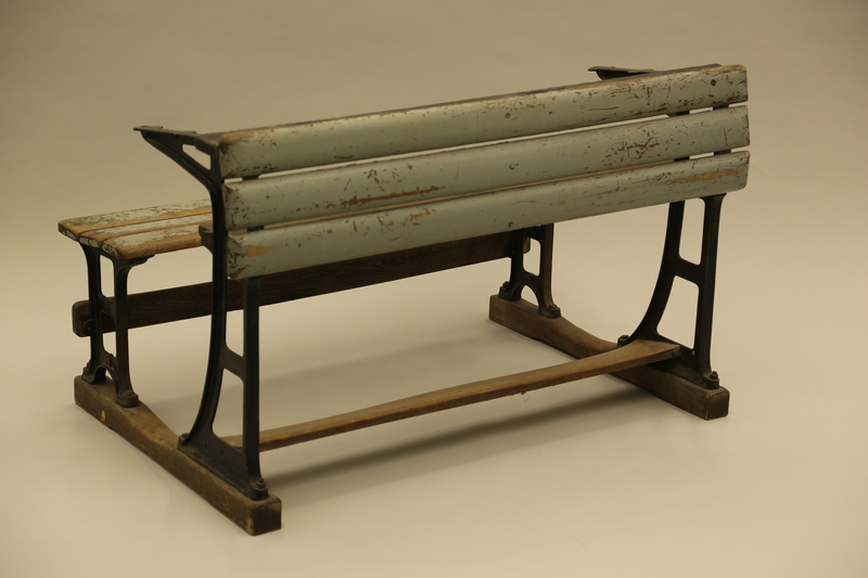 1990.44.7 3/4 view Slatted wooden desk with attached bench on wrought iron supports used in a Dresden schoolroom in Nazi Germany