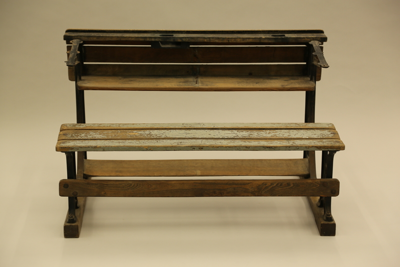 1990.44.7_002 back Slatted wooden desk with attached bench on wrought iron supports used in a Dresden schoolroom in Nazi Germany