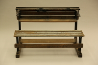 1990.44.7_002 back Slatted wooden desk with attached bench on wrought iron supports used in a Dresden schoolroom in Nazi Germany  Click to enlarge