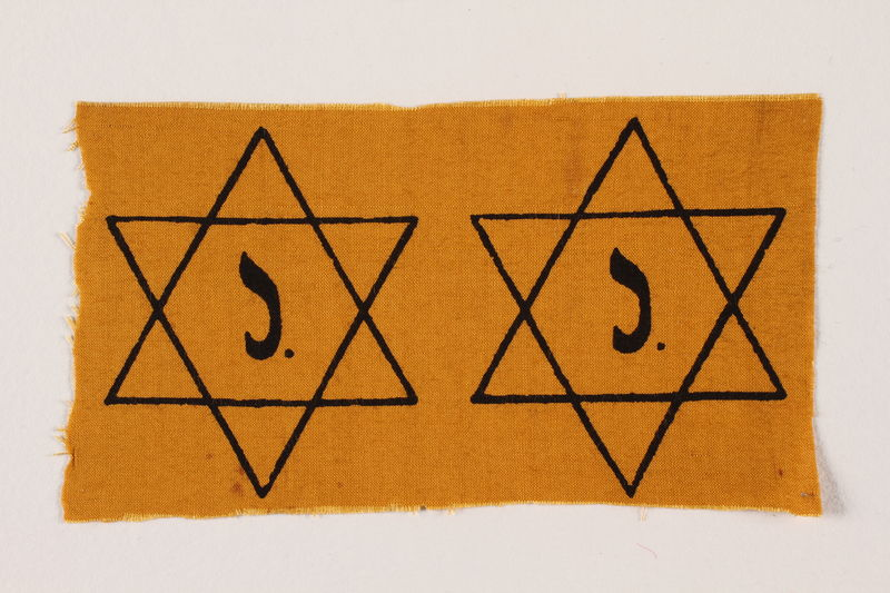2009.355.2 front Two unused Star of David badges with a J issued to a Jewish family