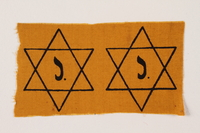 2009.355.2 front Two unused Star of David badges with a J issued to a Jewish family  Click to enlarge