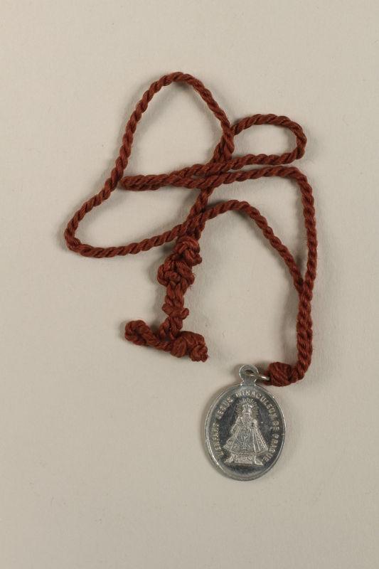 2009.359.2 front L'Enfant Jesus Miraculeux de Prague [Miraculous Infant Jesus of Prague] medallion given to an young Austrian Jewish woman