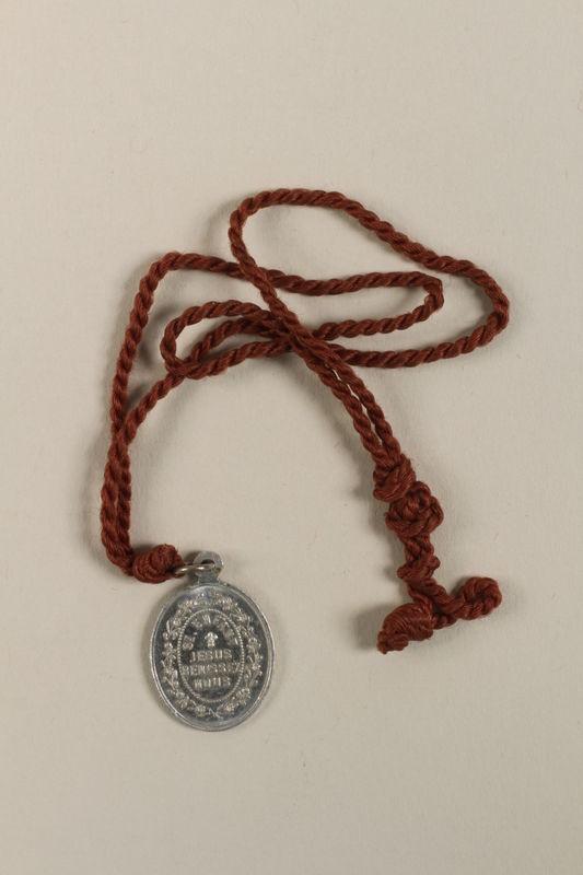 2009.359.2 back L'Enfant Jesus Miraculeux de Prague [Miraculous Infant Jesus of Prague] medallion given to an young Austrian Jewish woman