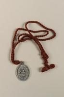 2009.359.2 back L'Enfant Jesus Miraculeux de Prague [Miraculous Infant Jesus of Prague] medallion given to an young Austrian Jewish woman  Click to enlarge
